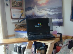 Here I am sitting on the bed and my computer is sitting on a board that is fastened to the shelf with a C Clamp.